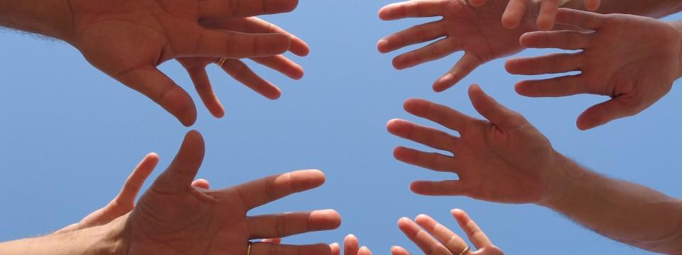 Tante mani che si incrociano e si uniscono di fronte al cielo azzurro